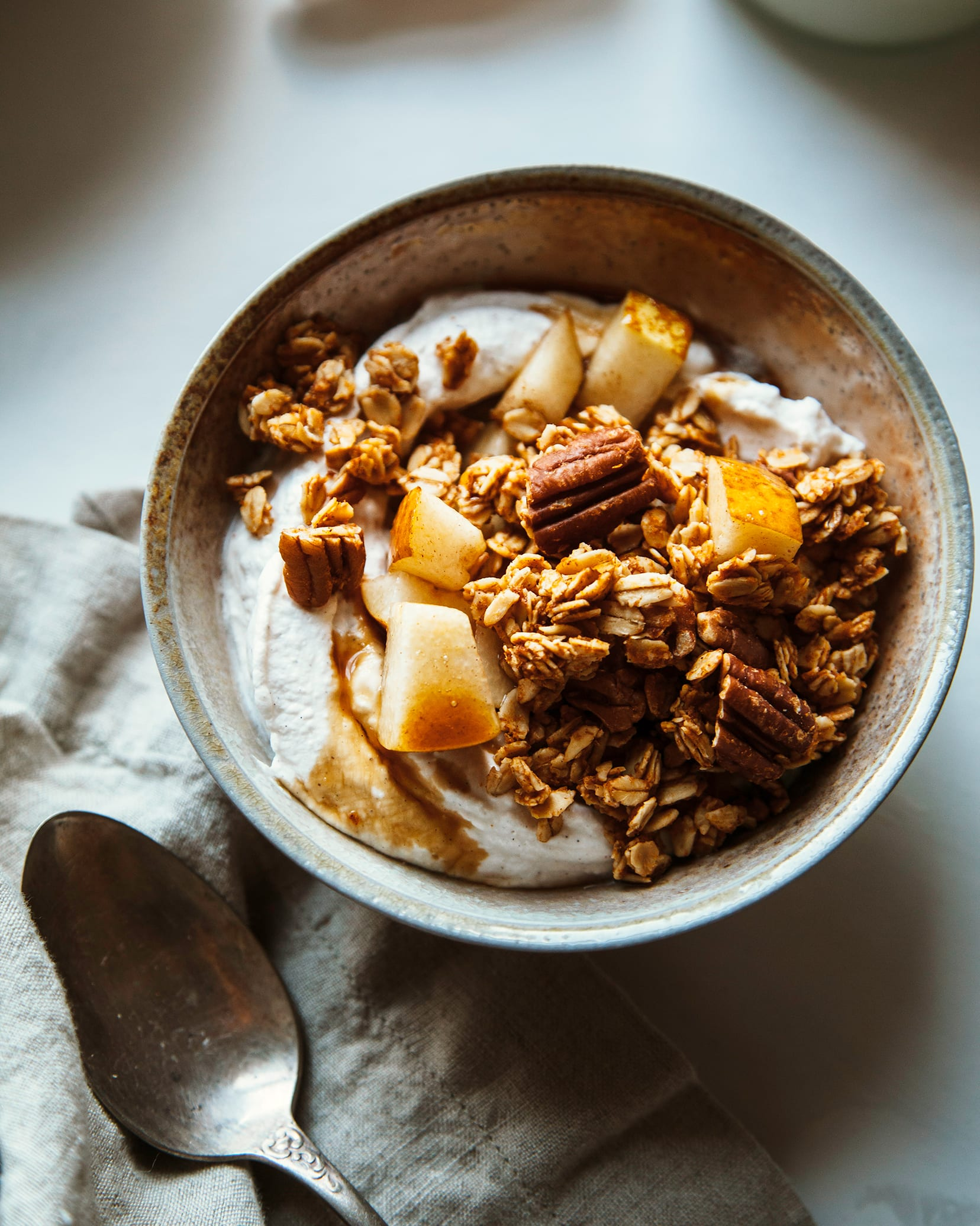Overhead shot of sweet potato granola in a bowl with chopped pear and coconut milk granola.