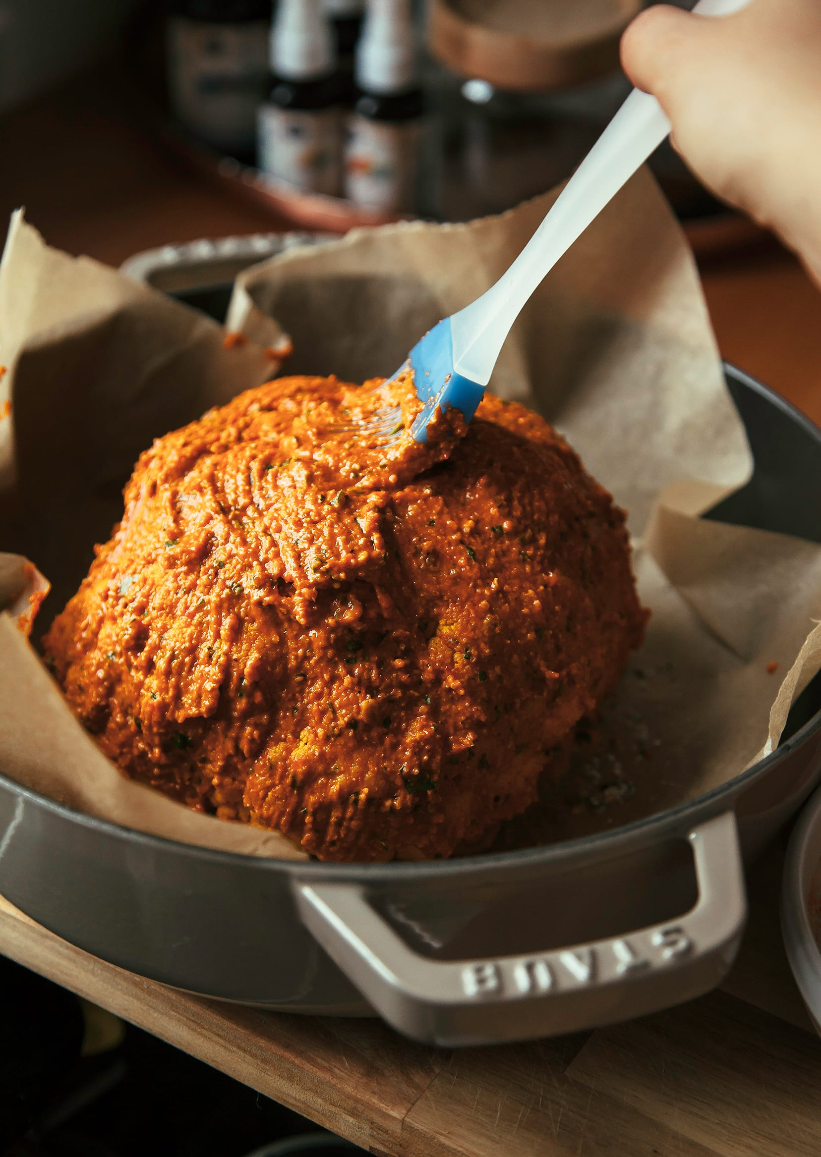 Image shows a hand brushing romesco onto the surface of a whole cauliflower.