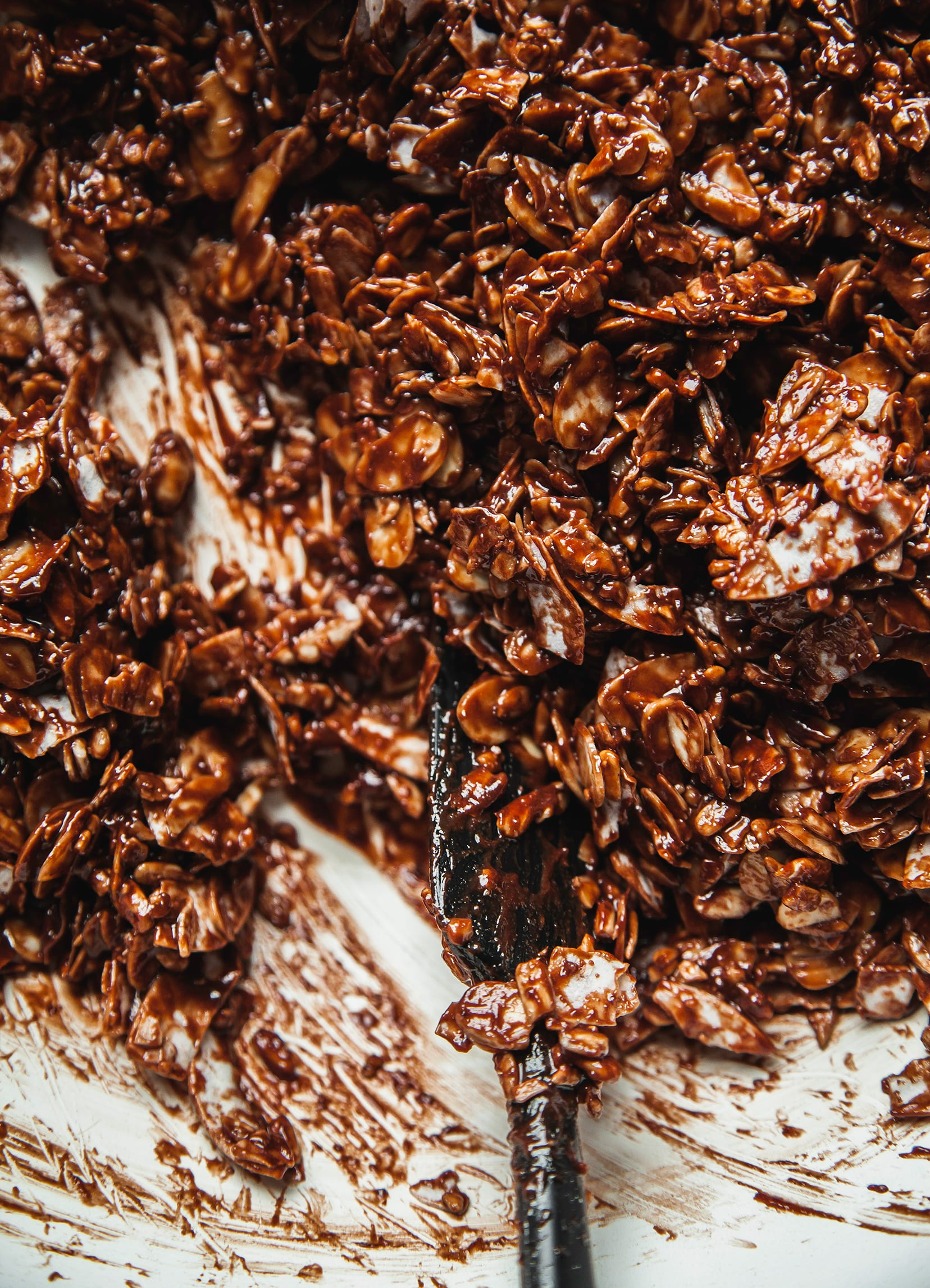 An overhead shot of chocolate sea salt granola being mixed together before baking.