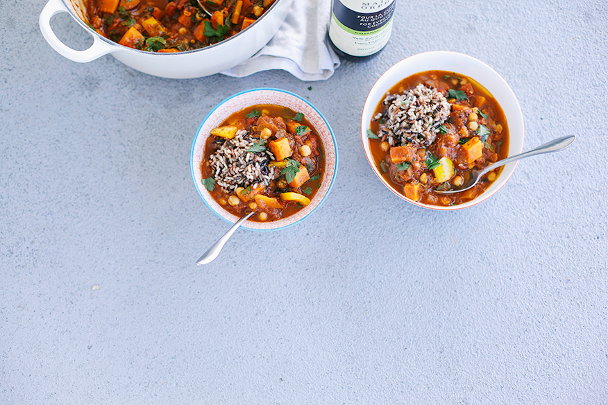 An overhead shot of bowls of Moroccan-inspired vegetable and chickpea stew on a light grey background. The stew is deep red and both bowls are garnished with a scoop of brown and wild rice mixture.