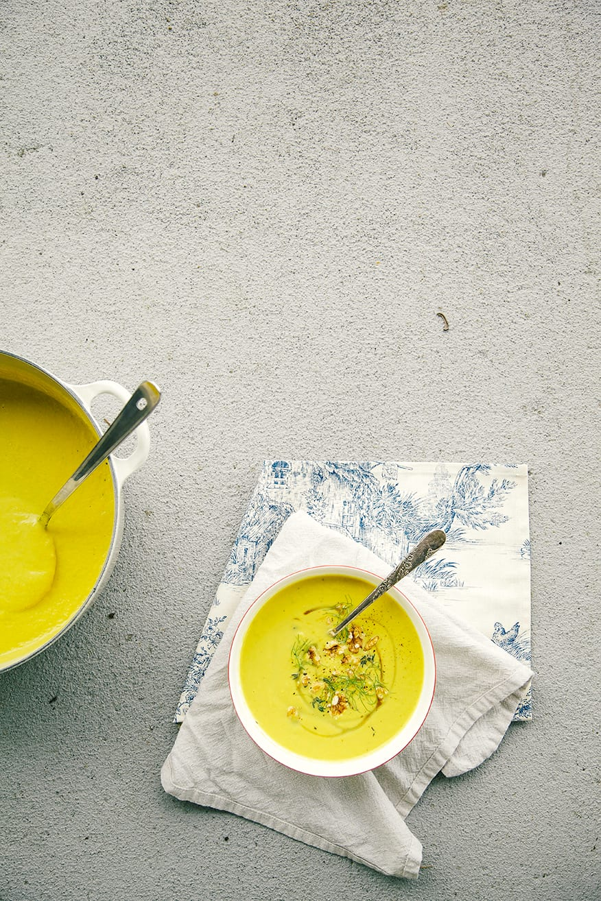 An overhead shot of fennel walnut soup with turmeric on a beige and blue napkin over a grey concrete background. The soup is bright yellow and garnished with toasted walnuts, fennel fronds and a drizzle of maple syrup.