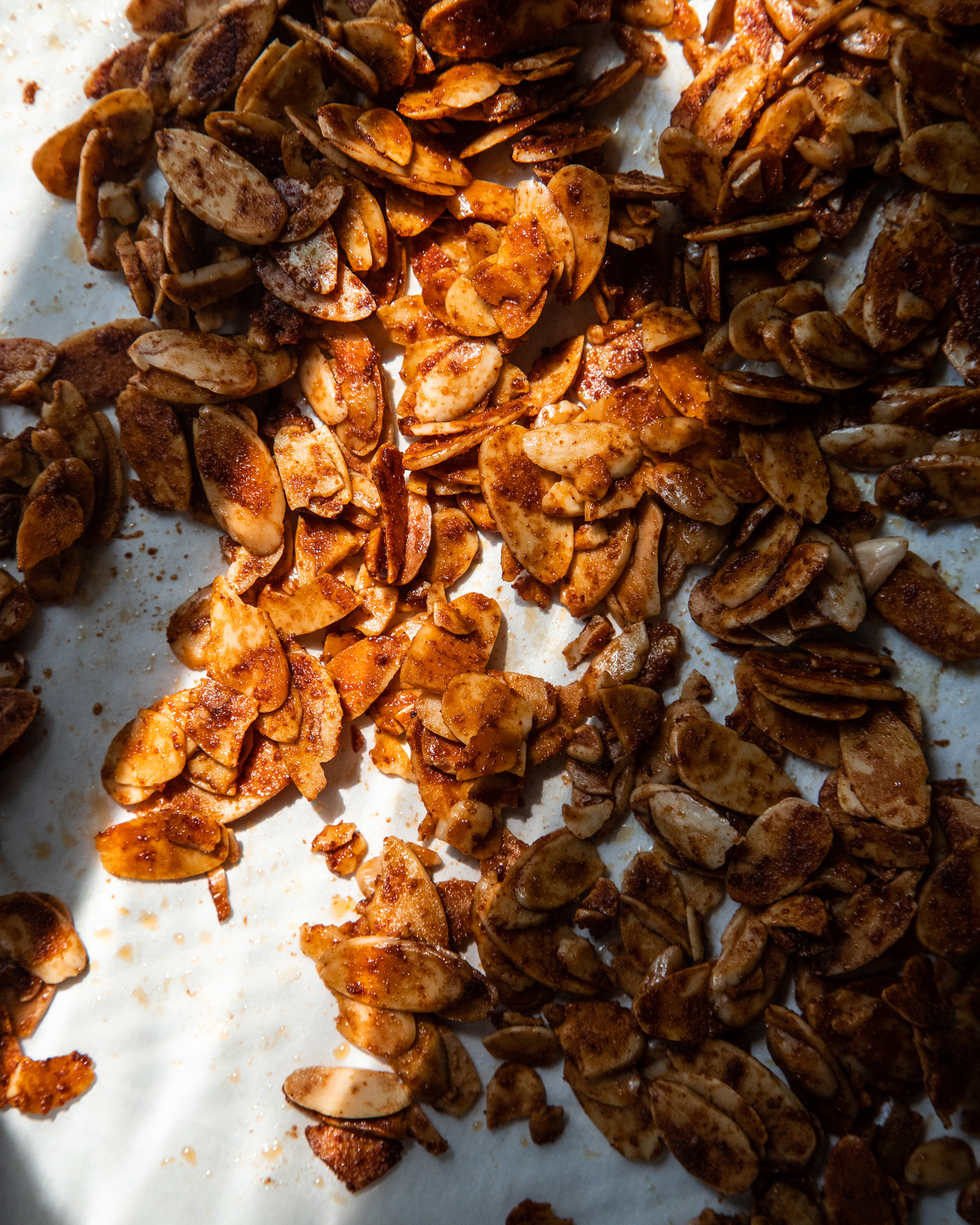 An overhead image of baked and deep brown sliced almonds in high contrast lighting.