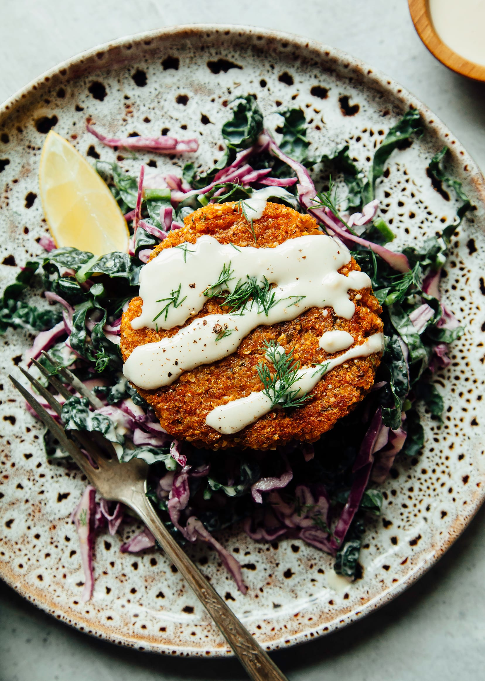 An overhead shot of a sweet potato cake pattie perched on top of a lemony slaw with a drizzle of tahini dressing. There is a lemon wedge to the side.
