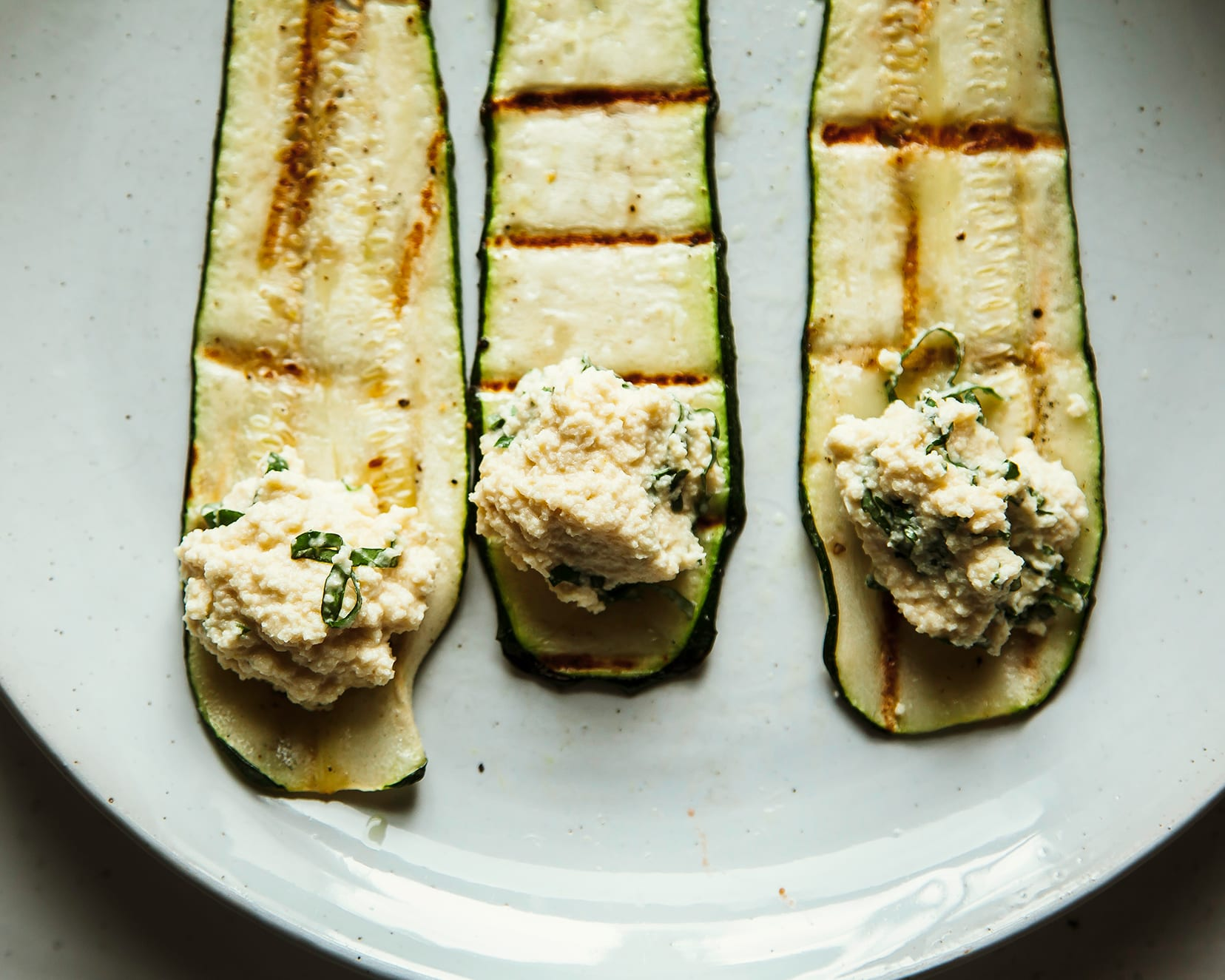 An overhead shot of three grilled strips of zucchini with dollops of herbed almond ricotta on top, ready to be rolled up.