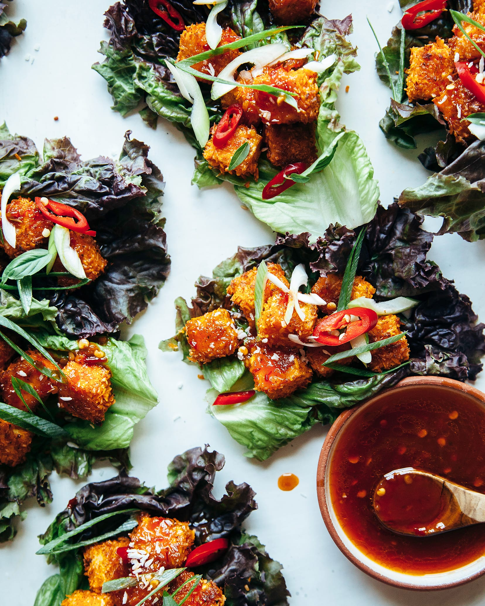 An overhead shot of crispy coconut tofu lettuce wraps with a bowl of sweet chili sauce for drizzling nearby. The tofu is wrapped in red leaf lettuce and the cubes of tofu are deep golden brown.
