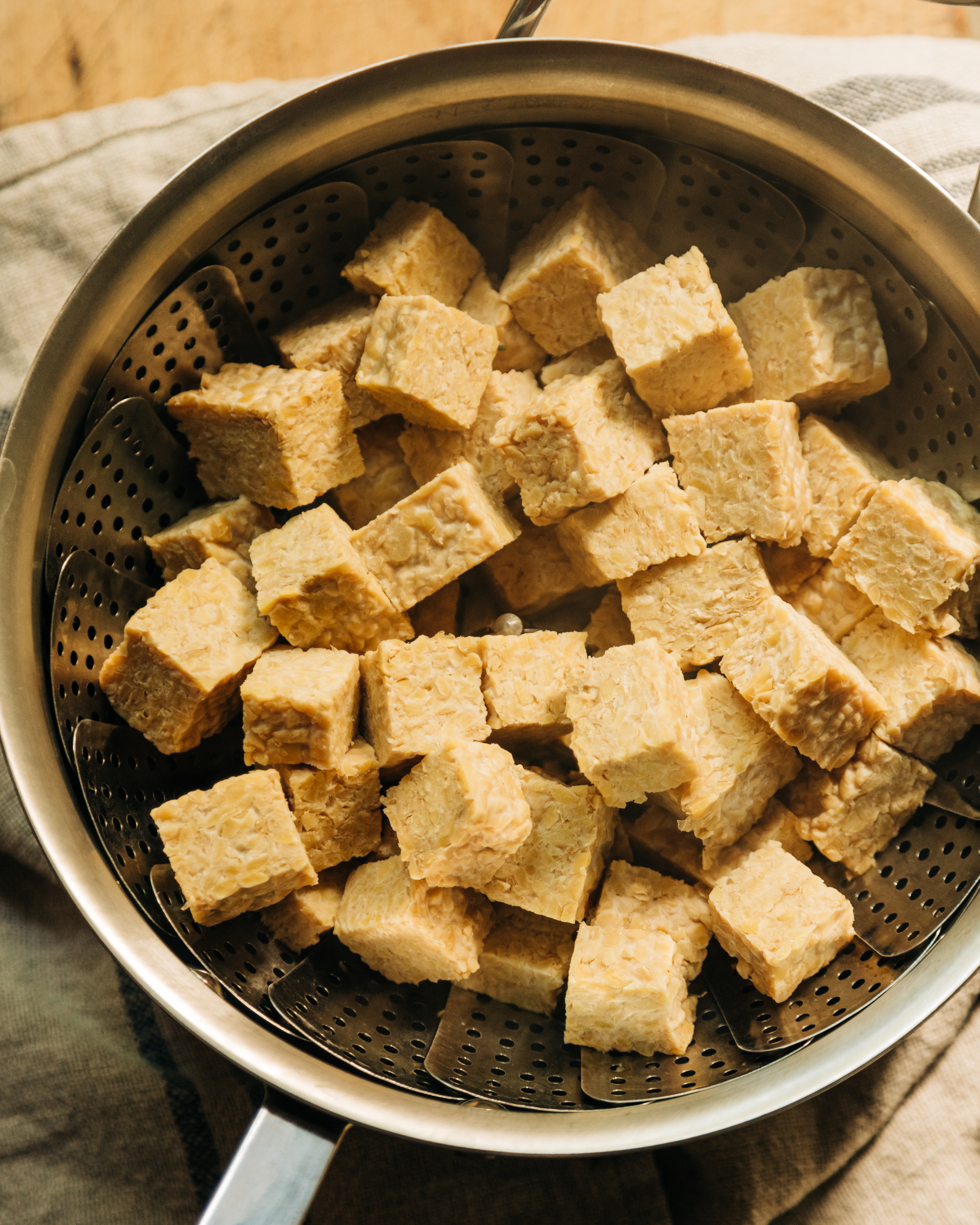 An overhead shot of tempeh chunks in a steamer basket that is set inside of a saucepan.