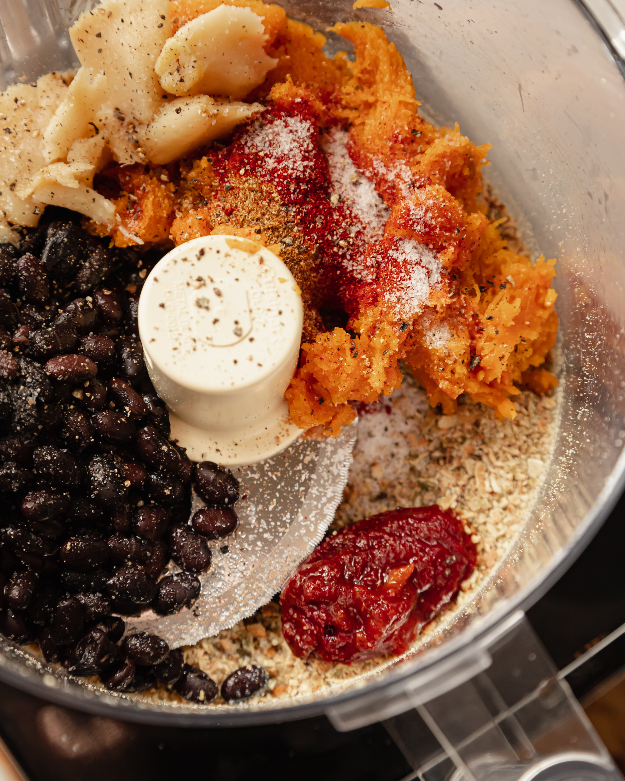 An overhead image of ingredients for a black bean dip in a food processor, pre-blending.