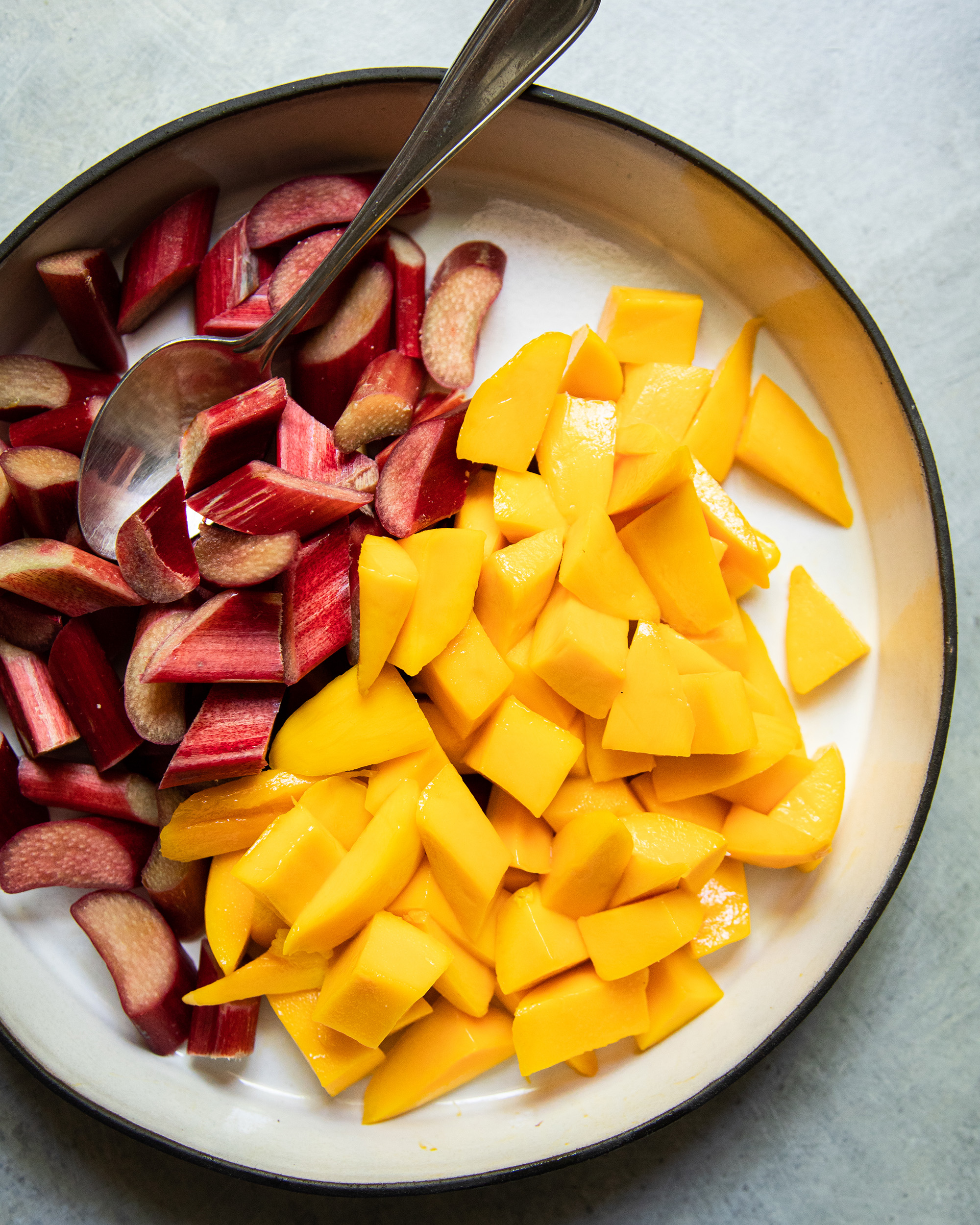 An up close, overhead shot of chopped rhubarb and mango pieces in a ceramic dish.
