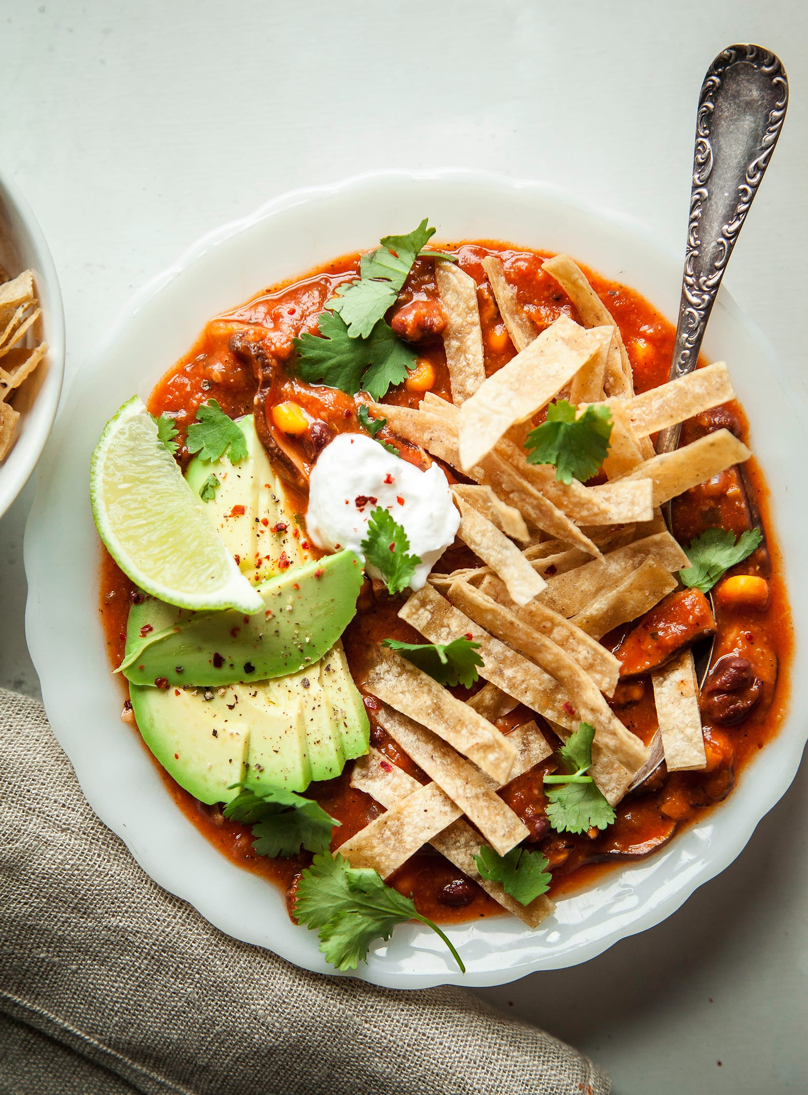 An overhead shot of smoky shiitake tortilla soup in a white bowl on top of a white background. The deep red soup is garnished with sliced avocado, a dollop of vegan sour cream, sliced avocado, tortilla strips, and fresh cilantro.