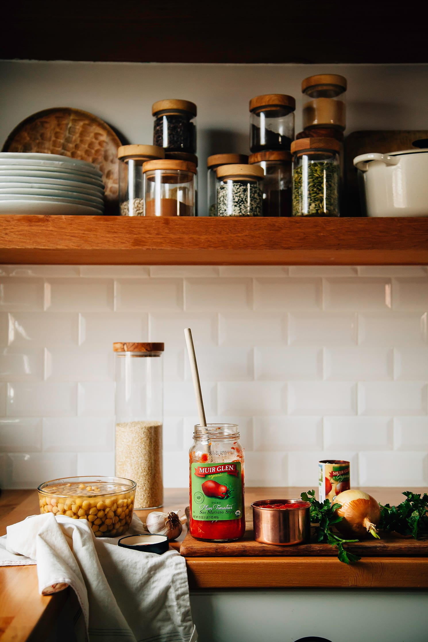 A head on shot of my butcher block kitchen counter with a jar of crushed tomatoes on top, along with a container of chickpeas, a container of millet, some parsley and an onion. White subway tile and open kitchen shelves are in the background.