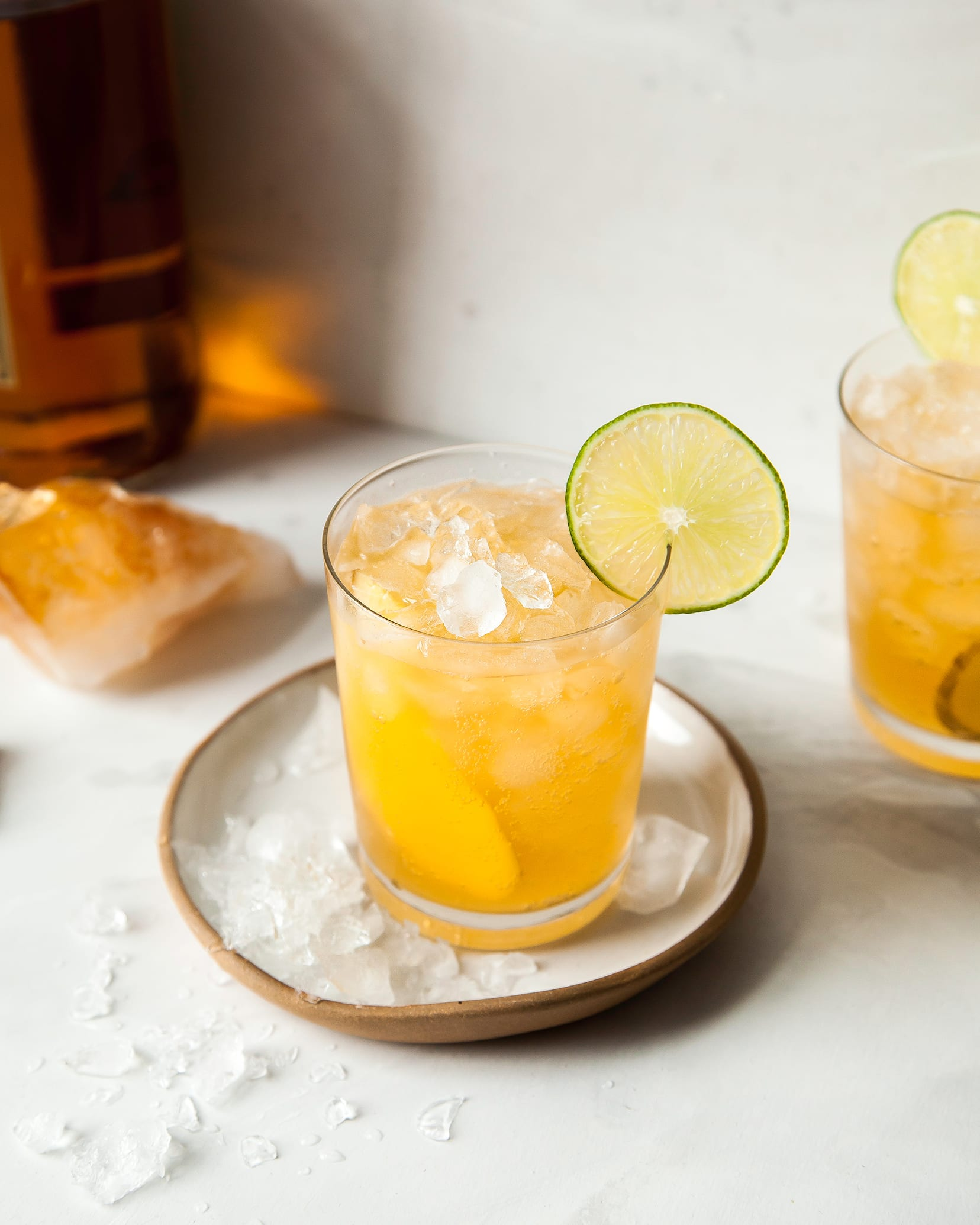 A straight-on photograph of a cold and golden beverage over crushed ice. The beverage is garnished with a wheel of lime.