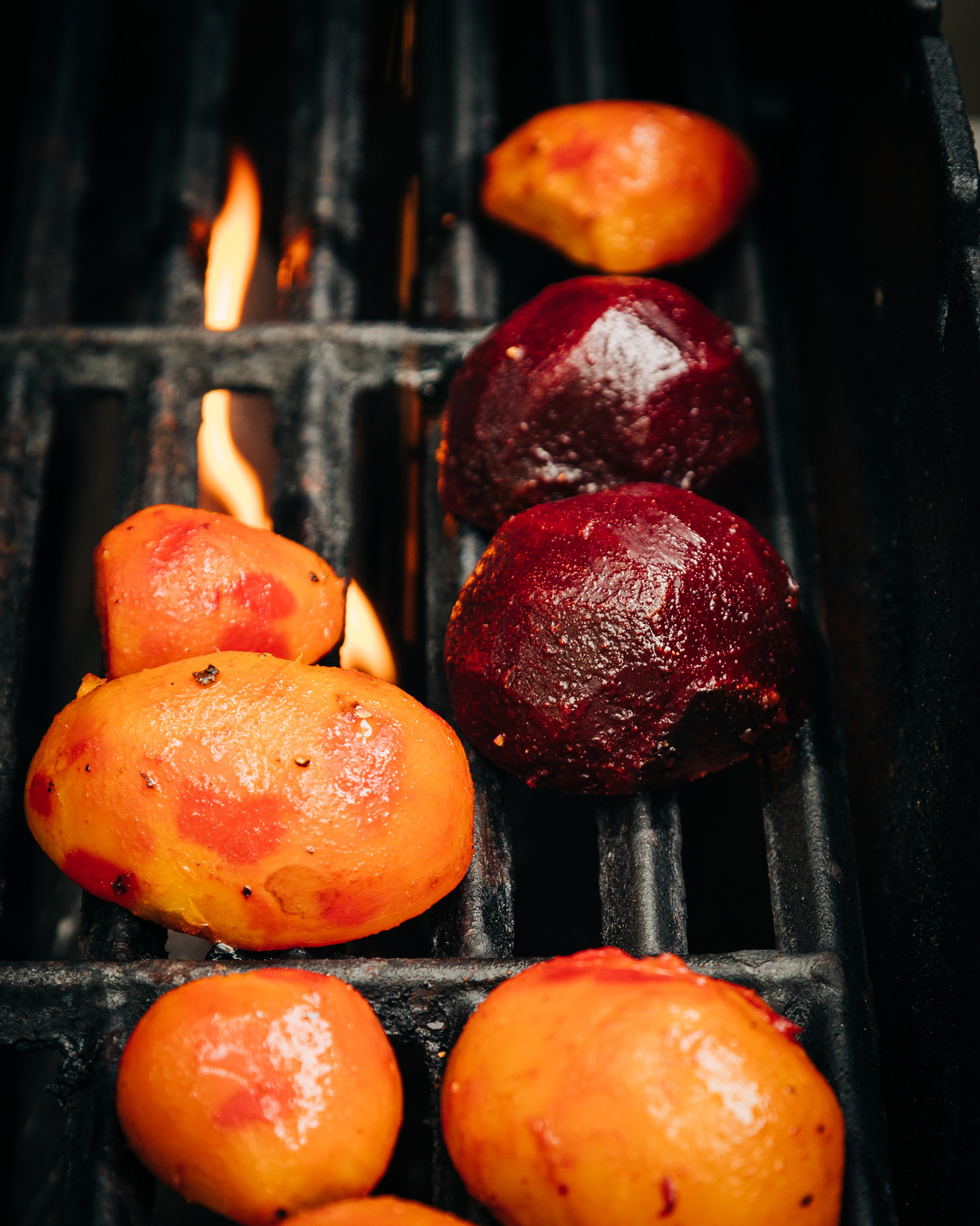 Image shows beet halves on a grill. A flame is kicking up in the background.