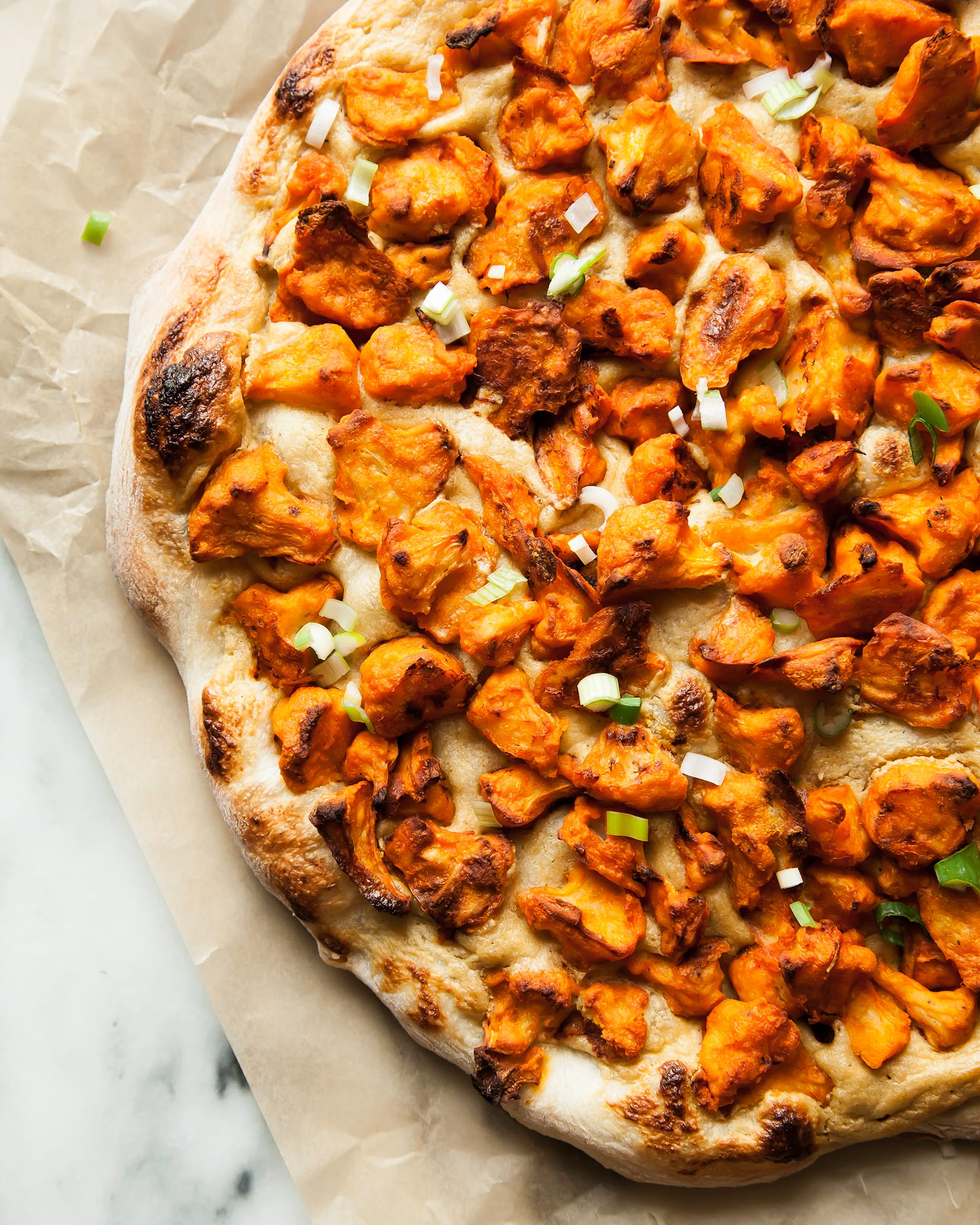 Image shows a baked pizza with Buffalo cauliflower on top.