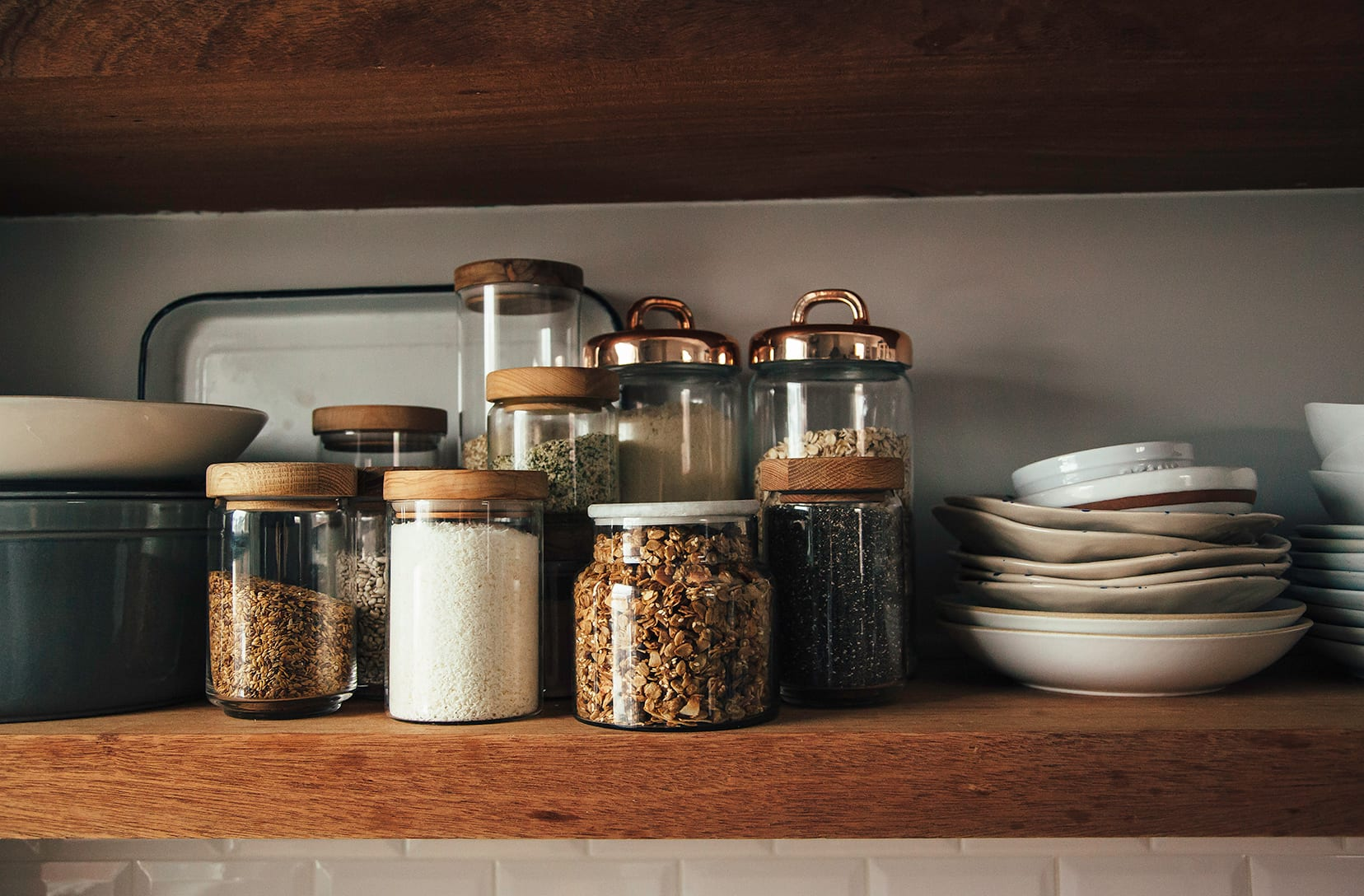 Image shows an open kitchen shelf with jars of seeds, grains, coconut, and granola.