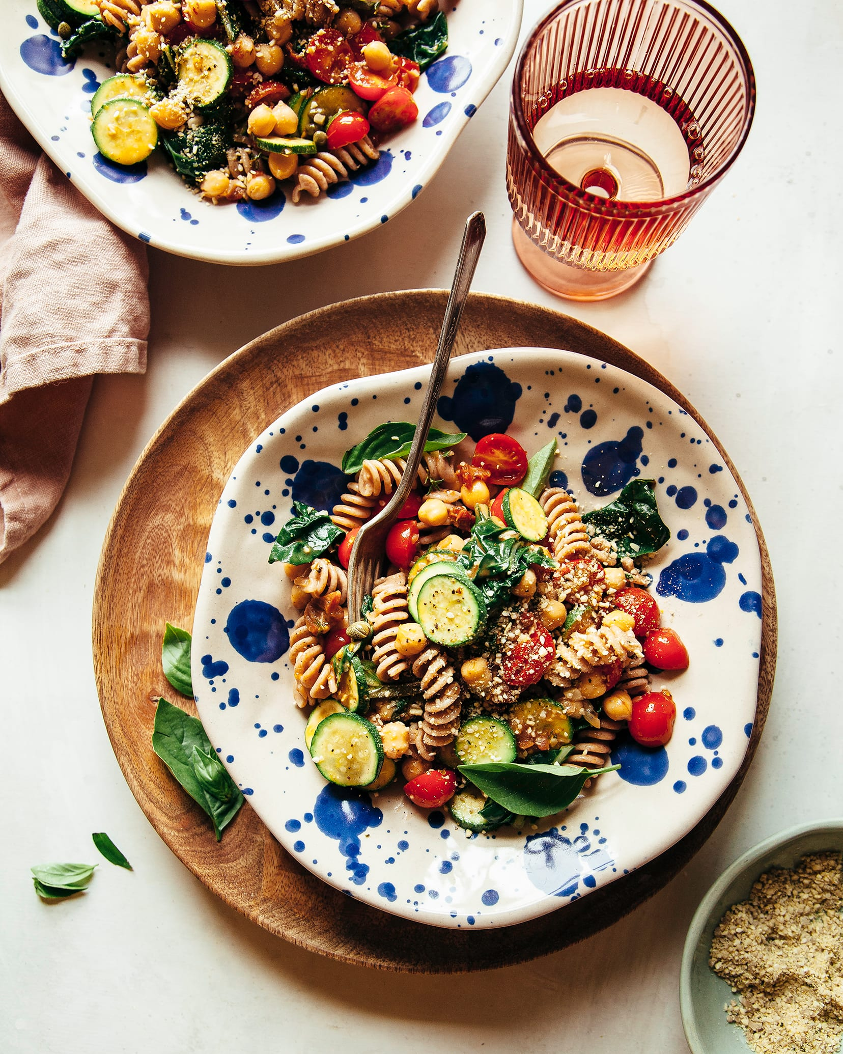 Overhead image shows a serving of rotini pasta in a blue splattered bowl. The pasta features cherry tomatoes, little zucchini rounds, chickpeas, greens, and a sprinkle of vegan