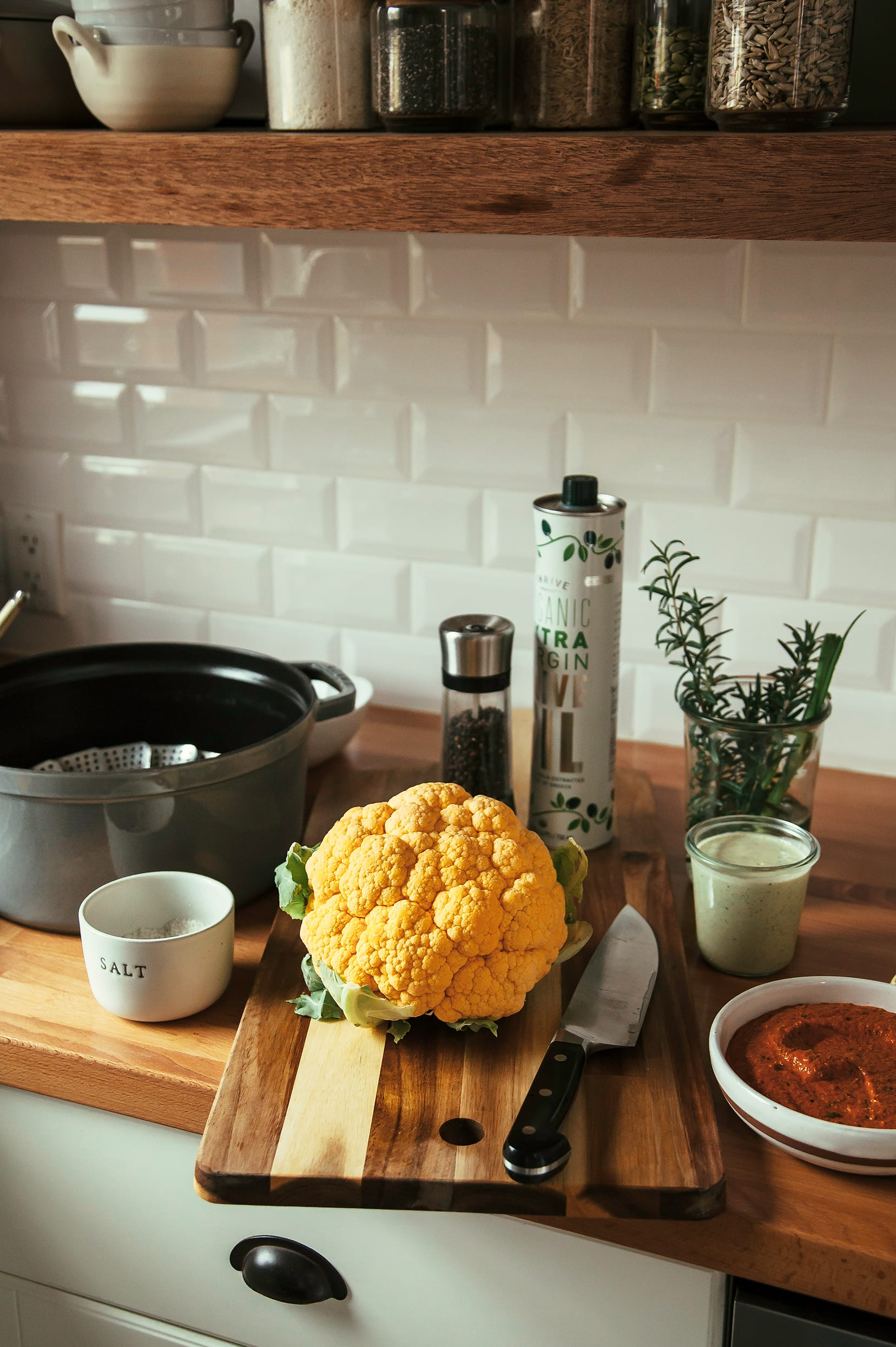 A whole cauliflower and other prepped ingredients are shown on a kitchen counter.