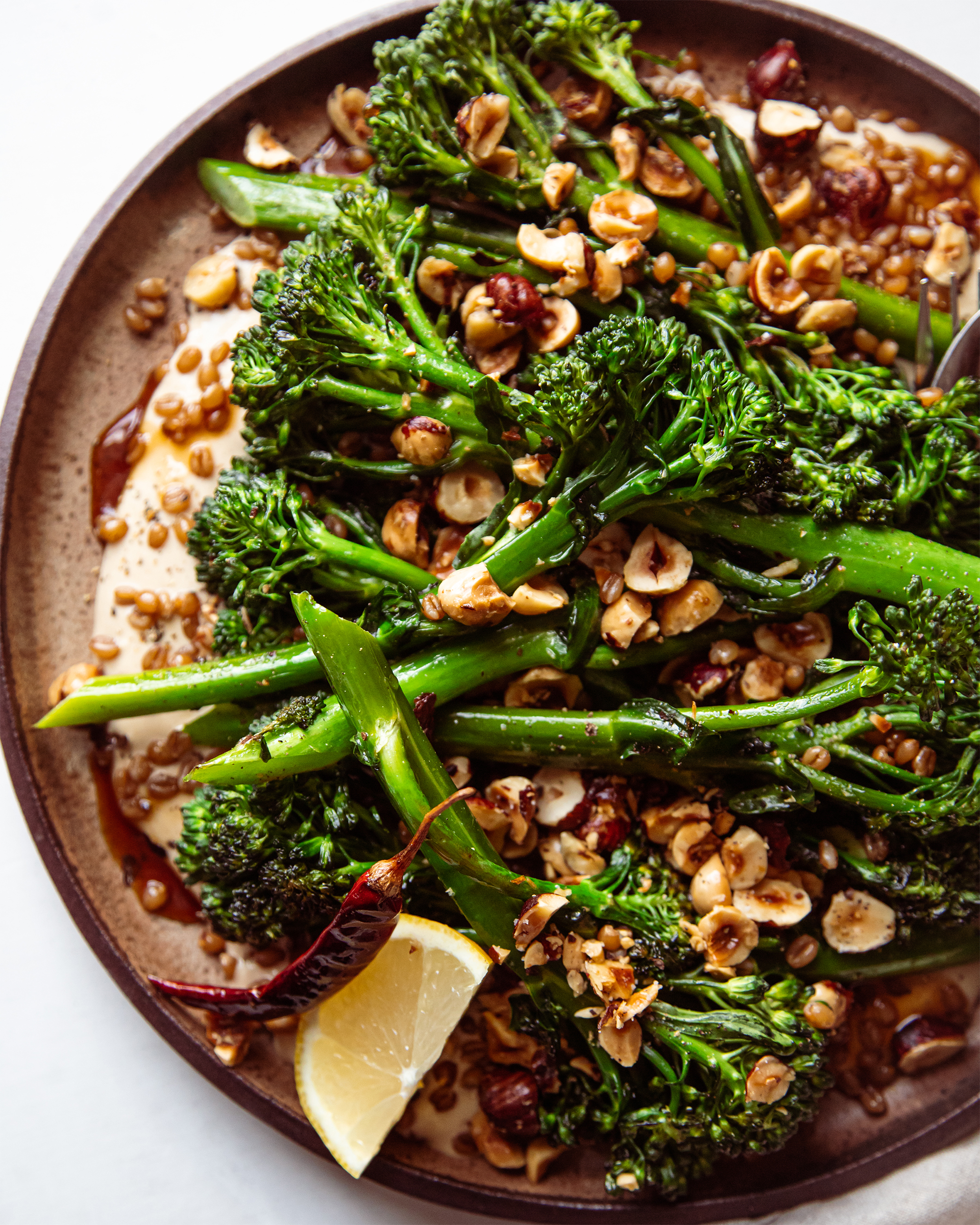 An up close and overhead shot of a broccolini dish on a brown plate.