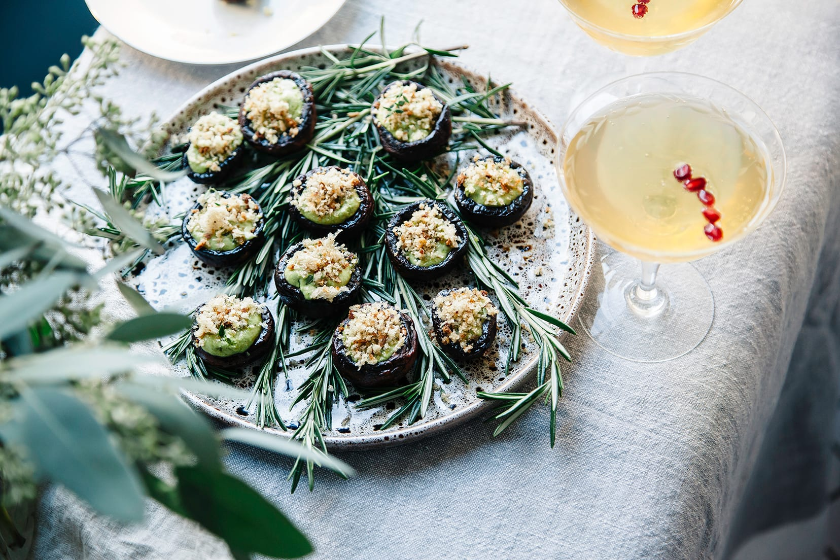 Image shows some stuffed mushrooms with a creamy green sauce and breadcrumbs.