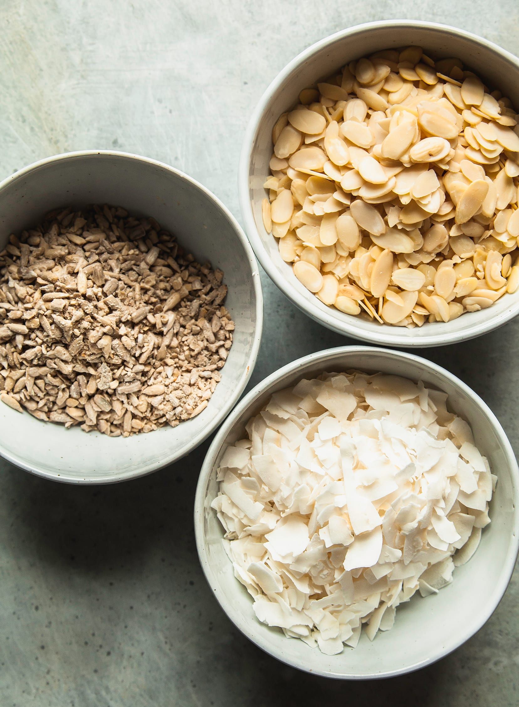 An overhead shot of ingredients in bowls: sunflower seeds, sliced almonds, and large coconut flakes.