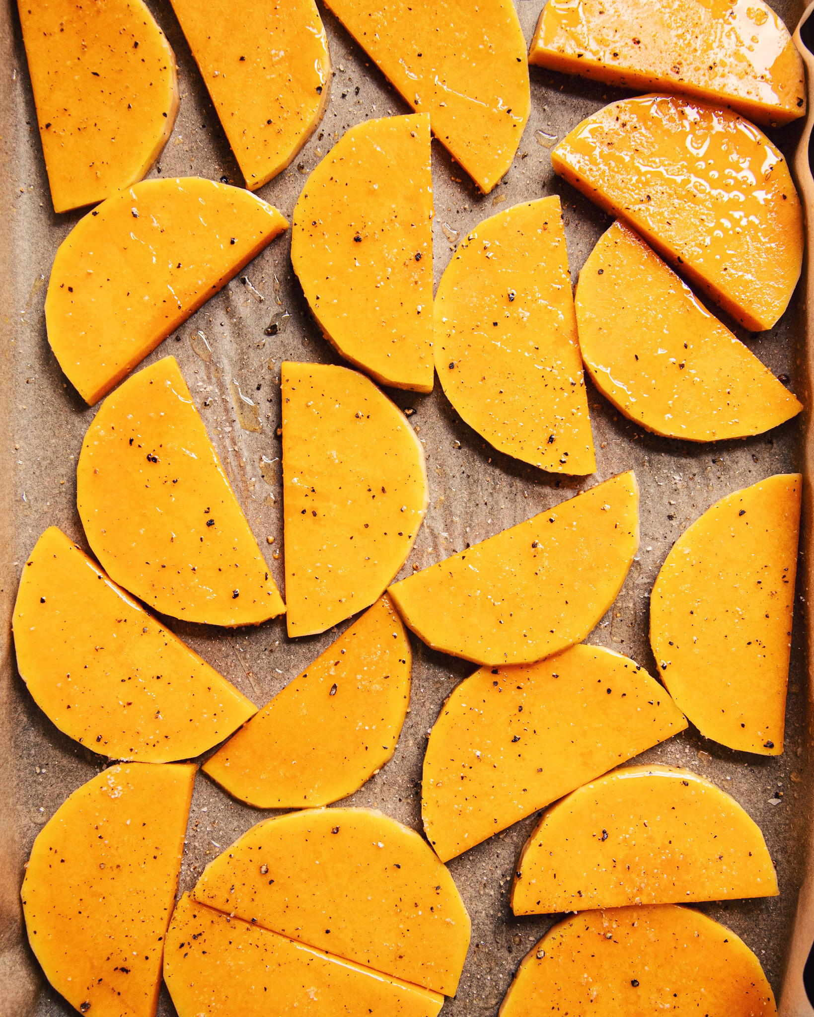 Overhead shot of slices of butternut squash on a parchment-lined baking sheet.