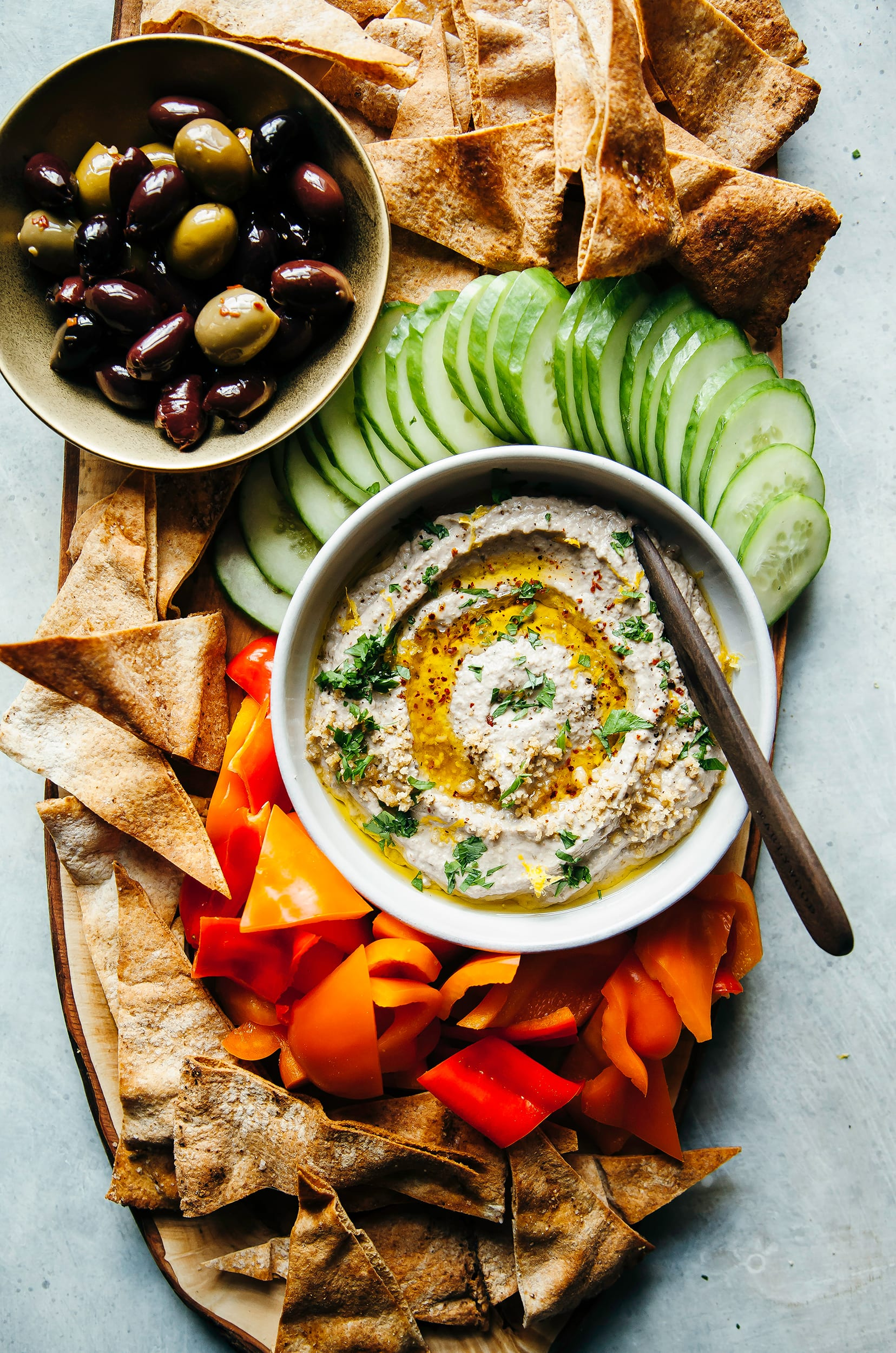 Image shows a board with a bowl of smooth eggplant dip, chopped vegetables, pita chips and olives.