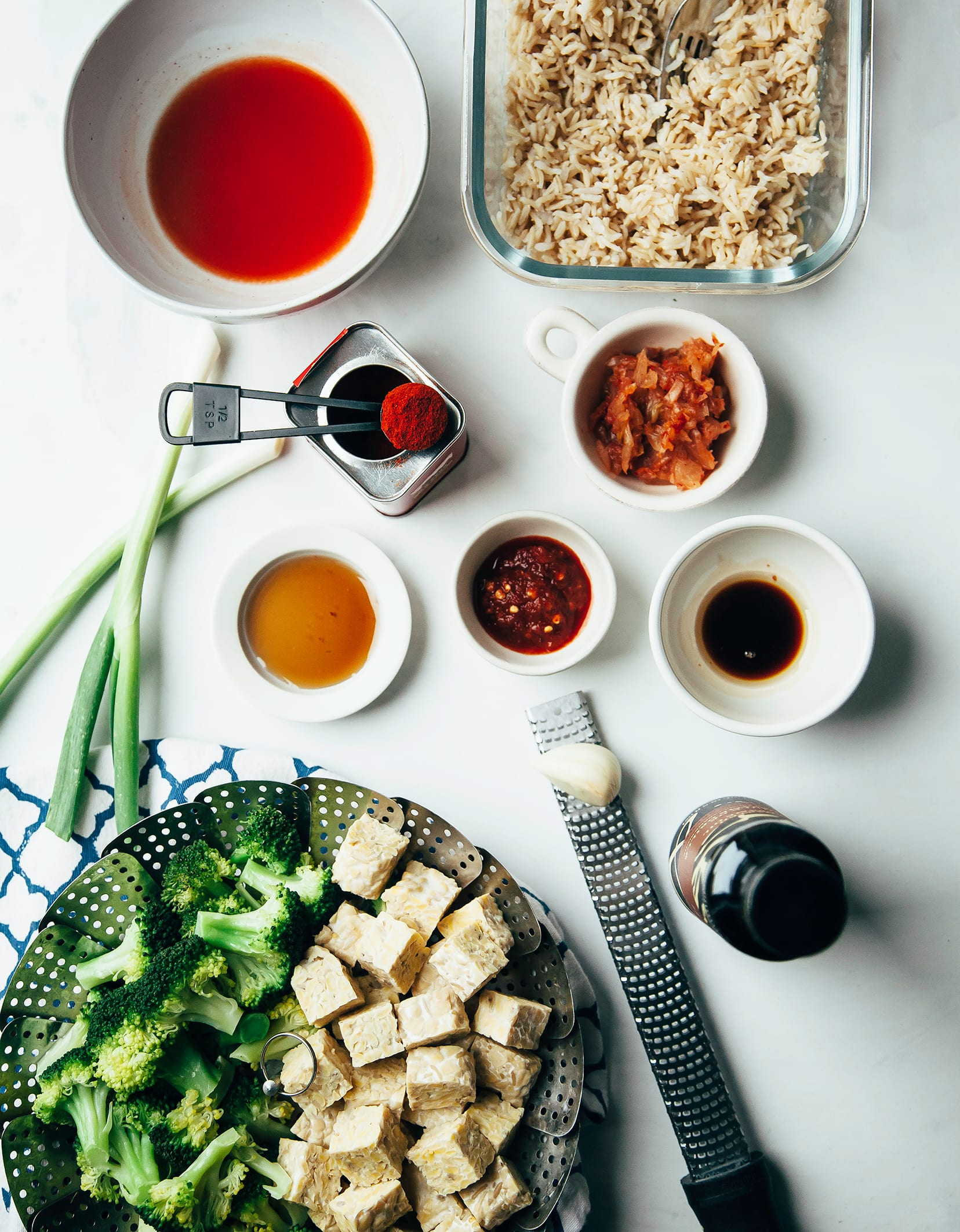 An overhead shot of ingredients for vegan kimchi fried rice on a white background.