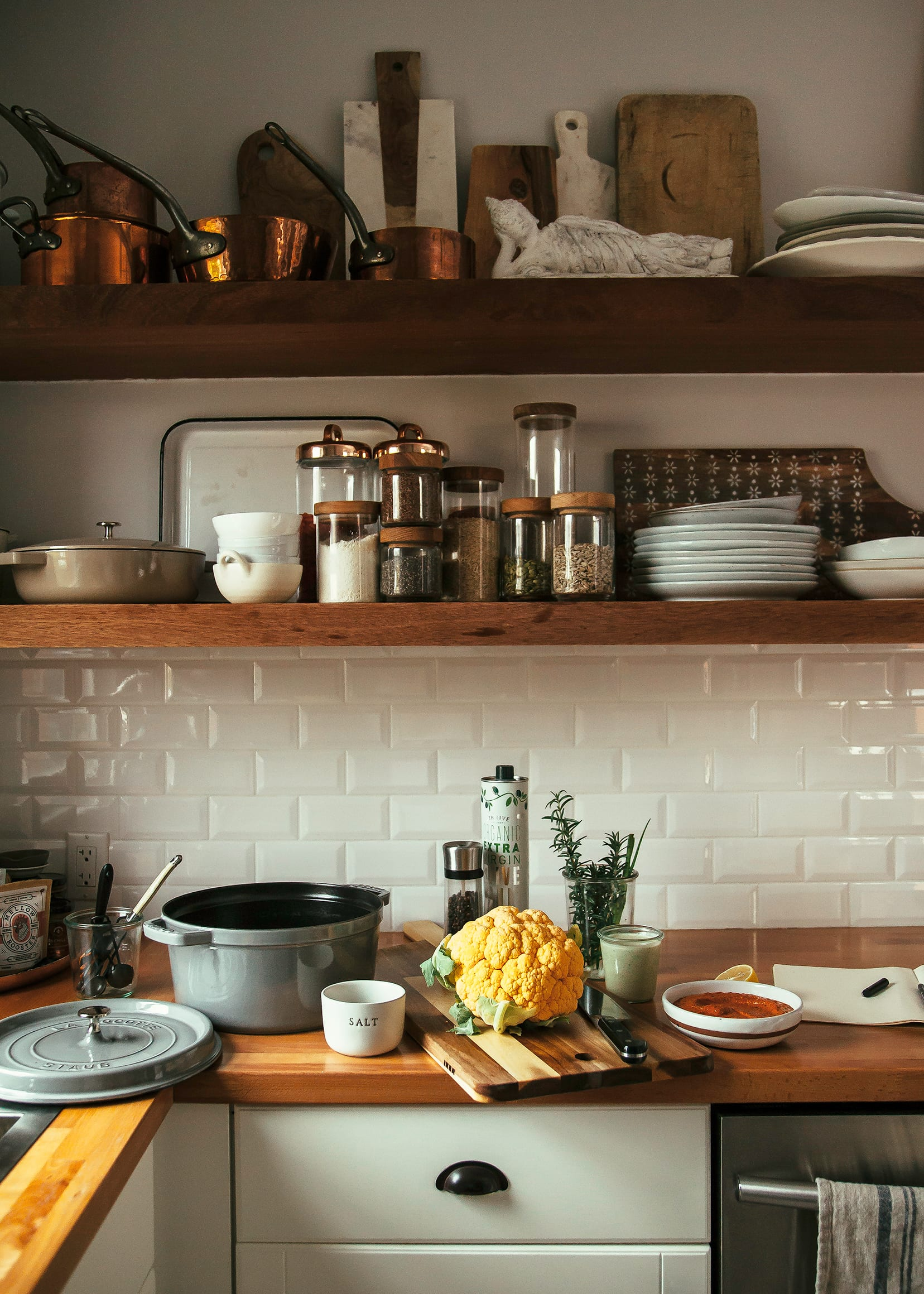A kitchen scene shows a cauliflower and other prepped ingredients on top of a butcher block counter with open shelving in the background.