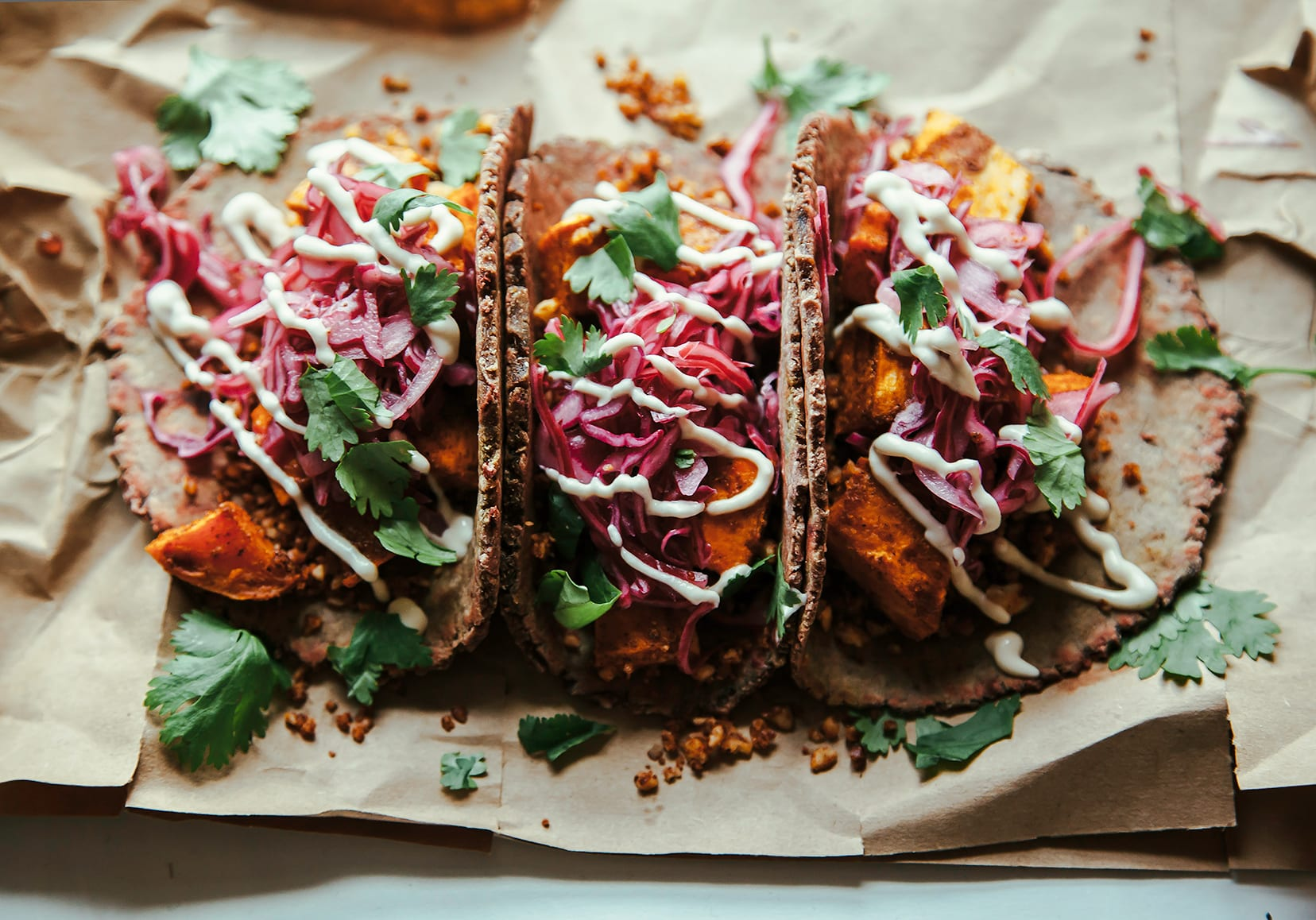 A 3/4 angle shot of 3 sweet potato tacos drizzled with a creamy white sauce and topped with chopped cilantro.