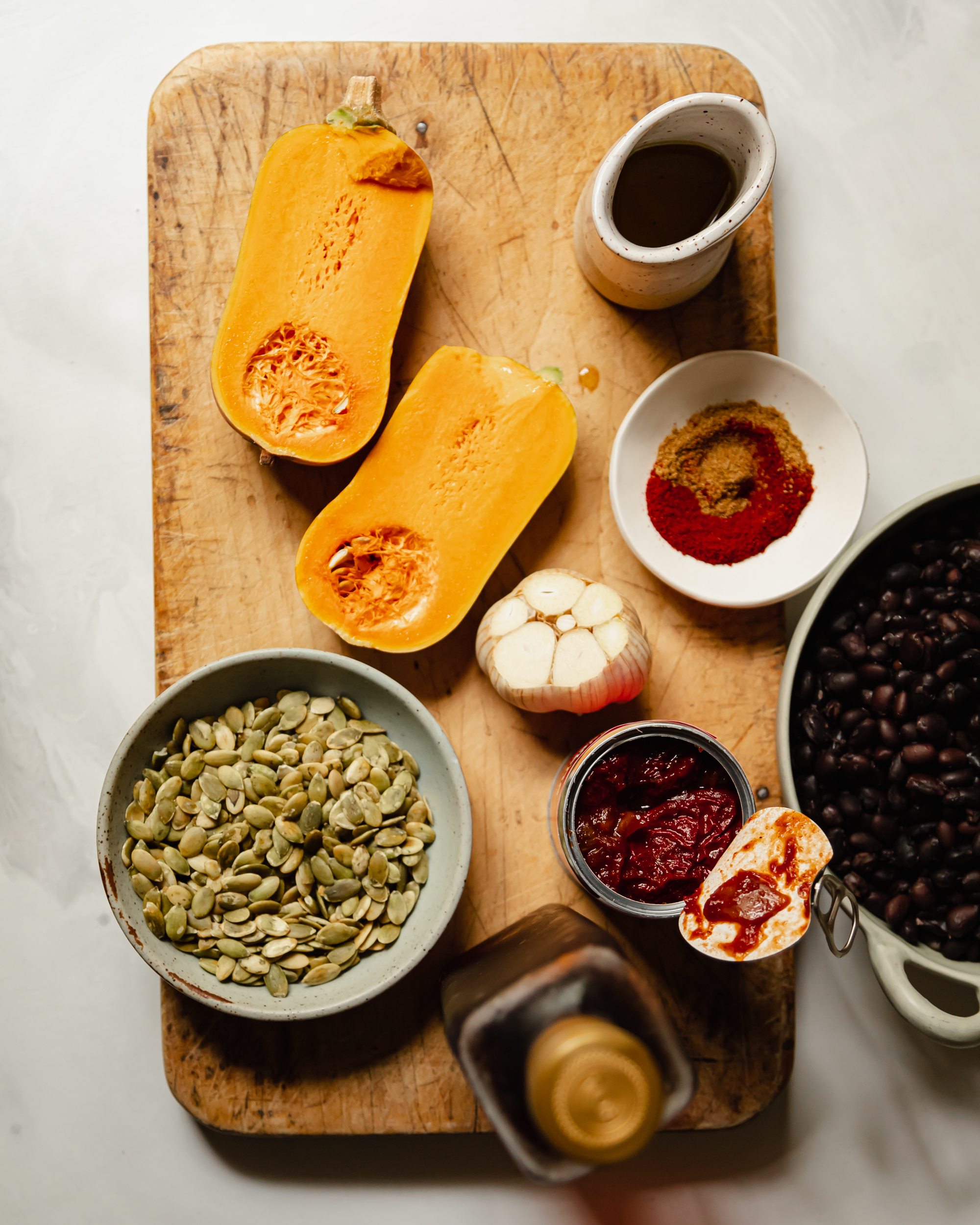 An overhead shot of ingredients used in a black bean dip with roasted squash and garlic.