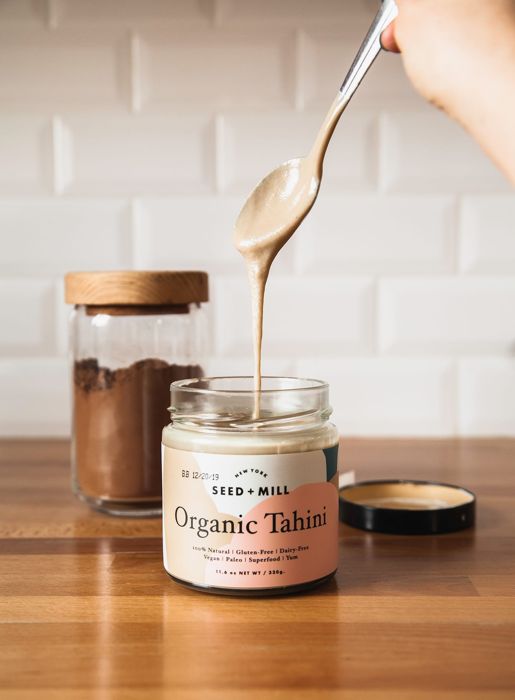Image shows a spoon lifting out of a jar of tahini with tahini dripping off of the spoon.