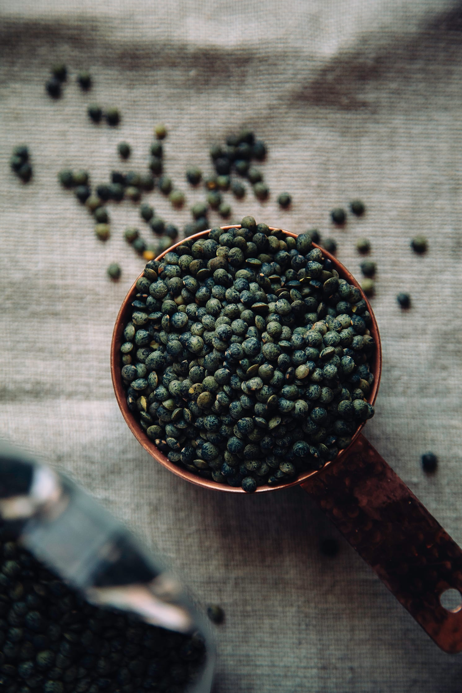 Overhead shot of dry French lentils in a copper measuring cup