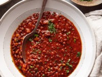 Image taken from overhead shows wide bowls of a deep red soup with little flecks of chopped parsley. A bowl of the chopped parsley is nearby.
