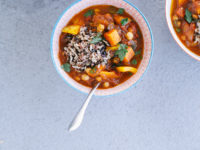 An overhead shot of a Morocco-inspired vegetable and chickpea stew with a scoop of mixed brown rice on top. The soup is in a red patterned bowl on top of a grey background in evening light.