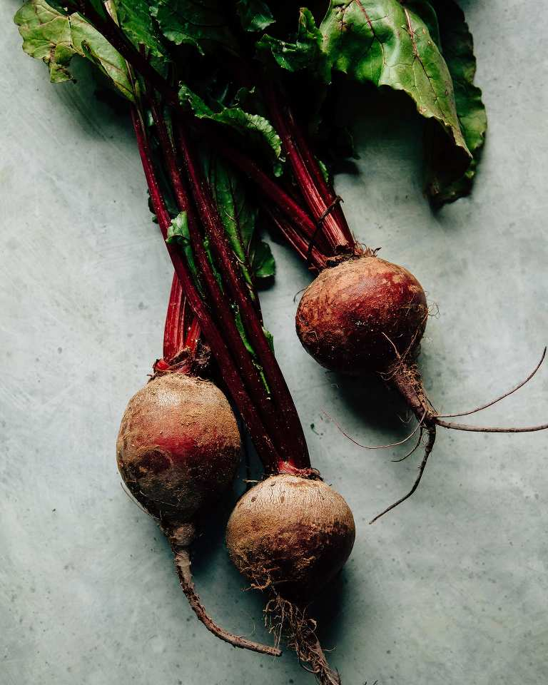 Overhead shot of a bunch of beets with their greens on a blue background.