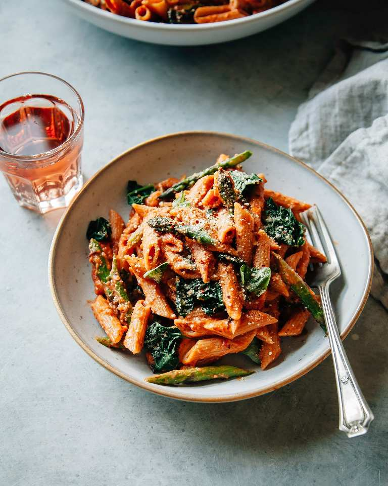 Overhead shot of finished and styled double rosé pasta with asparagus and kale. It is in an individual serving bowl with a glass of rosé wine to the side.