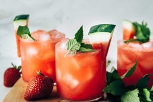 Photo displays finished glasses of sparkling strawberry watermelon limeade, garnished with wedges of watermelon and mint.