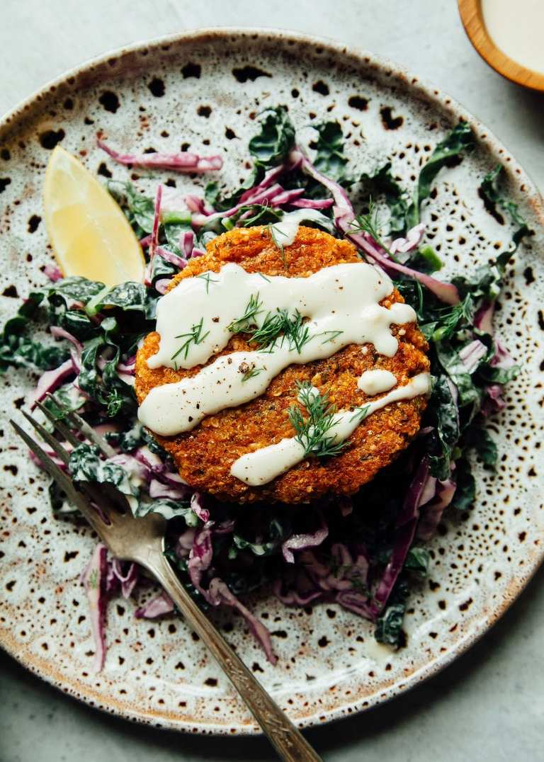 An overhead shot of sweet potato cakes perched on top of a lemony slaw with a drizzle of tahini dressing.