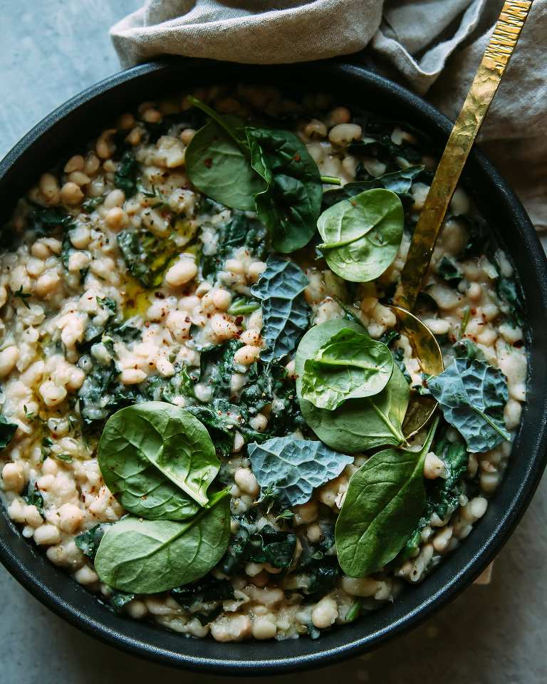 An overhead shot of creamy white beans with greens in a skillet with a gold ladle.