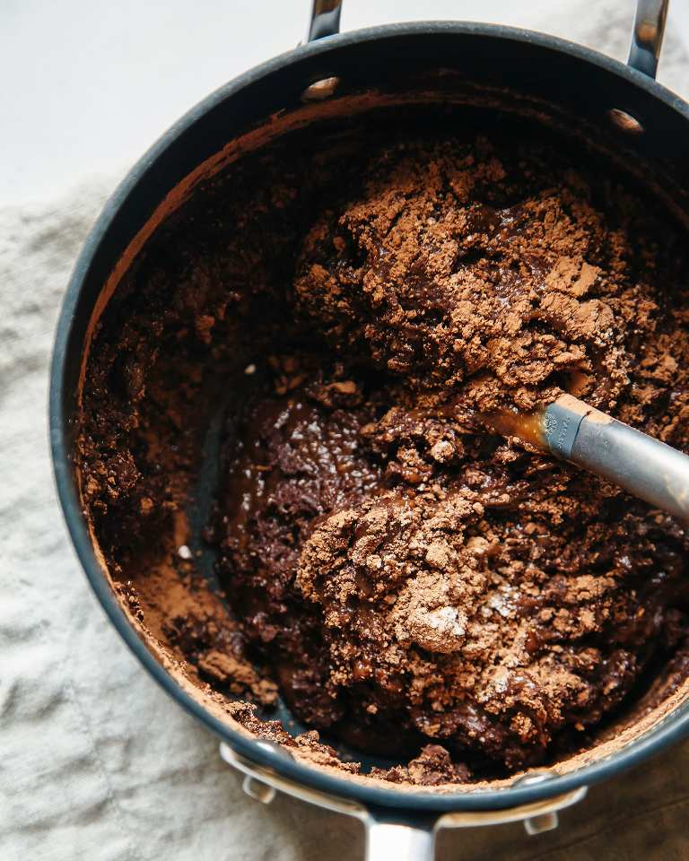 An overhead shot of melted chocolate being mixed with dry ingredients in a medium saucepan.