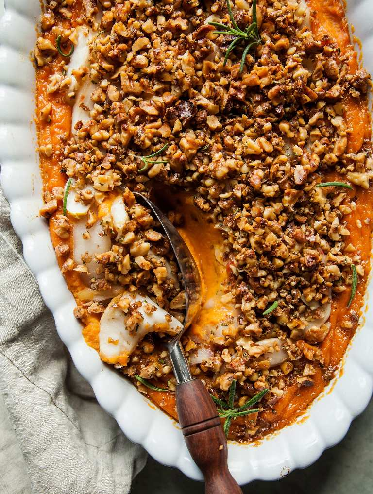 Overhead shot of vegan sweet potato casserole with apples and crunchy rosemary walnuts sprinkled on top.