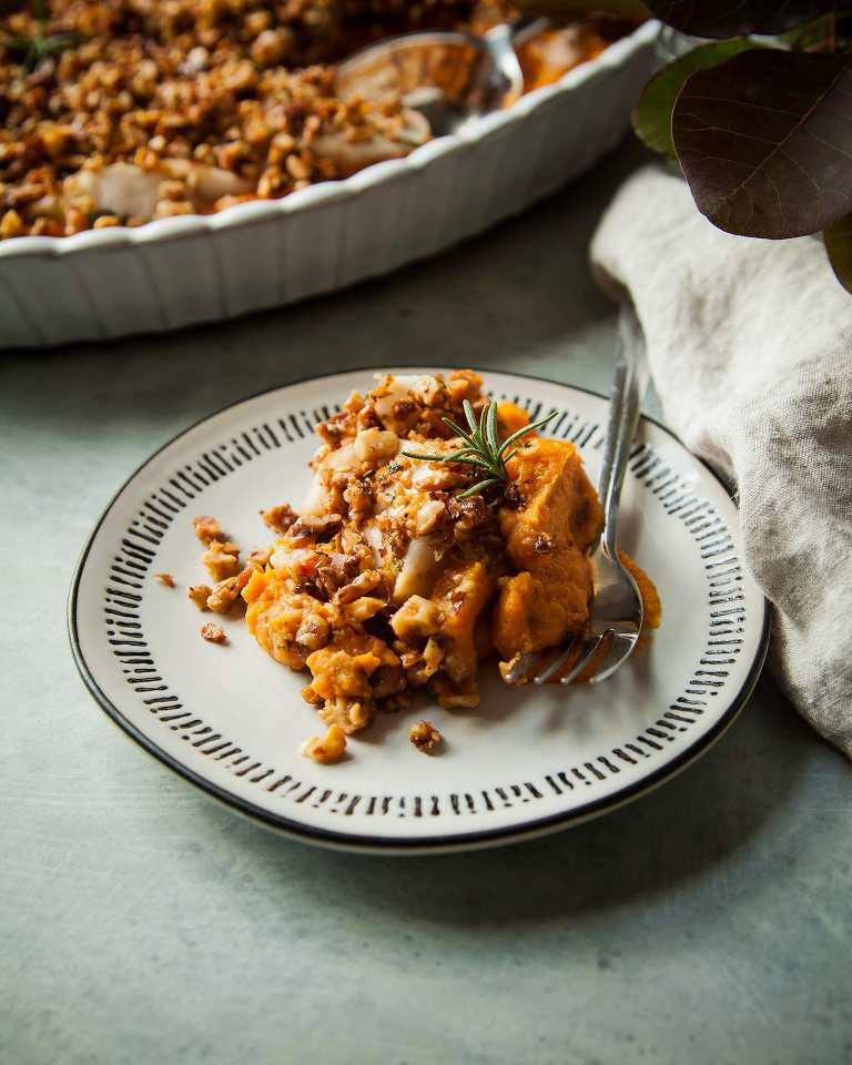 Side view of an individual serving of vegan sweet potato casserole with apples and crunchy rosemary walnuts.