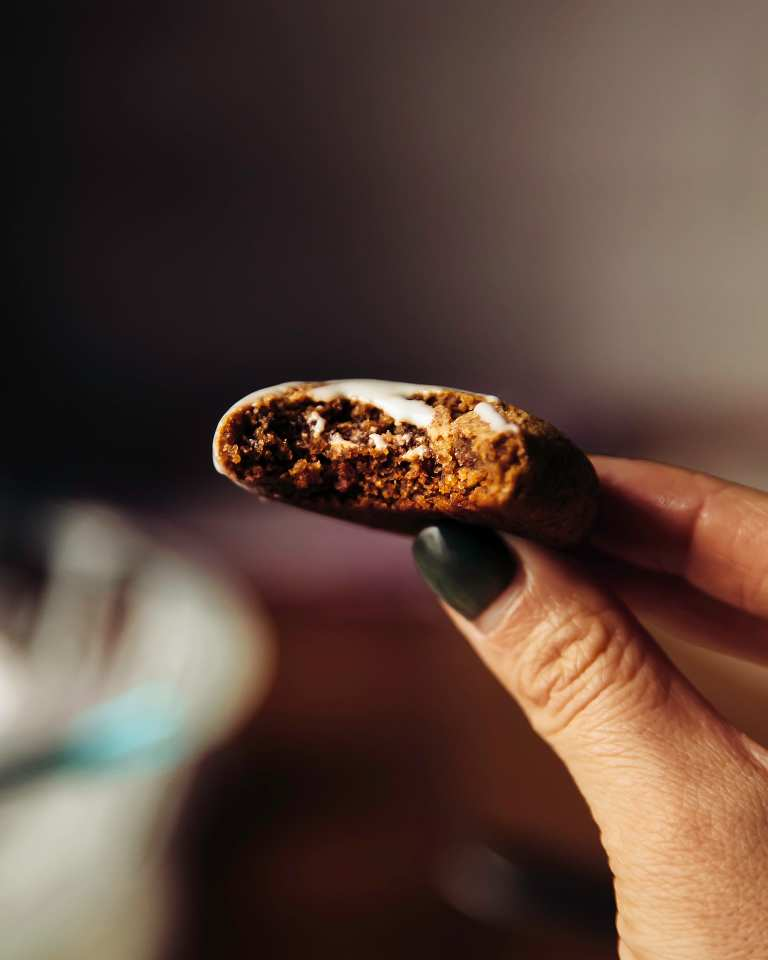 Head-on image of a grain-free ginger molasses softie that has been bitten into, revealing a moist and crumbly center.