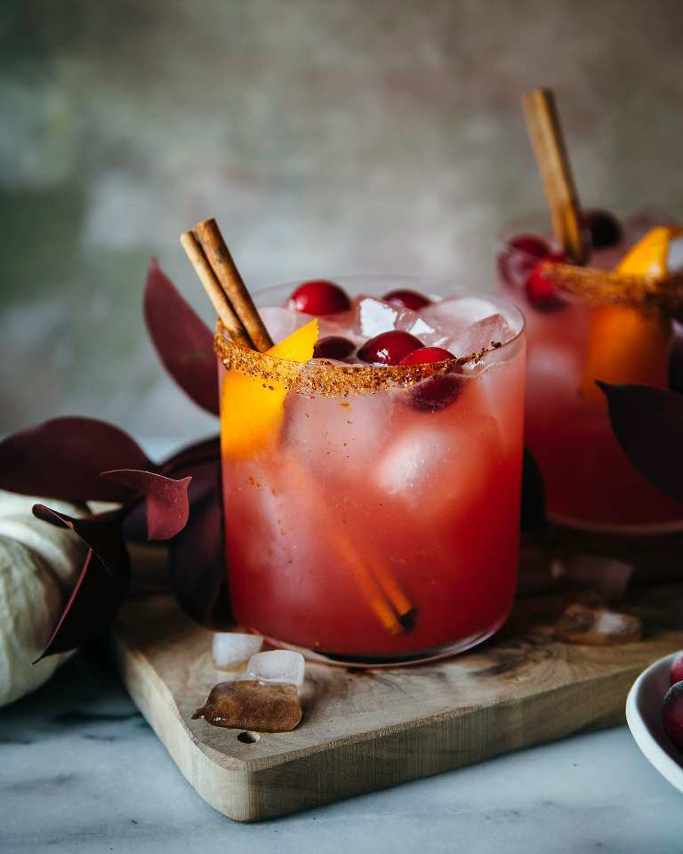 a head on shot of spiced cranberry orange margaritas garnished with cinnamon sticks and orange peels