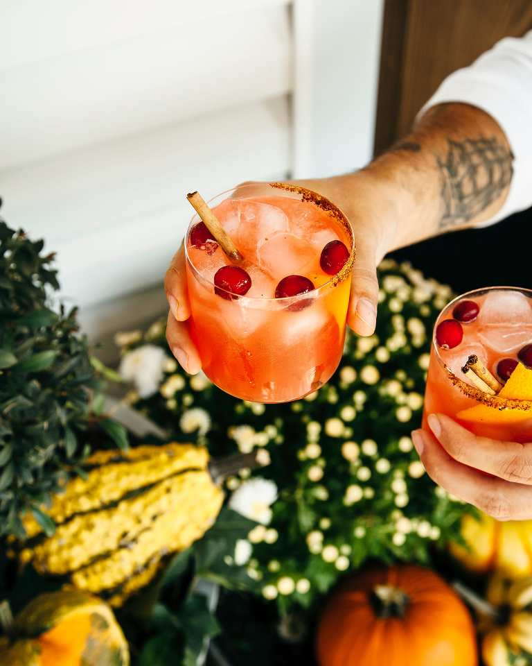 A pair of hands holding out two cocktails on the rocks in front of some Fall mums and pumpkins. Photo is taken outdoors in indirect light.