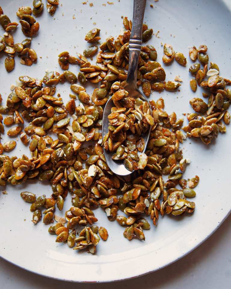 An up close shot of candied pumpkin seeds on a pale blue-white plate with a spoon.