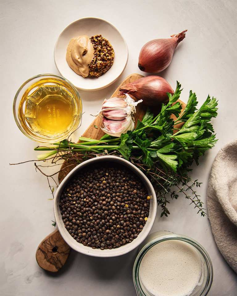 An overhead shot of the ingredients used for a stewed lentil dish. There's shallots, garlic, grainy and Dijon mustard, white wine, parsley, thyme, French lentils, and a cream made out of cashews.