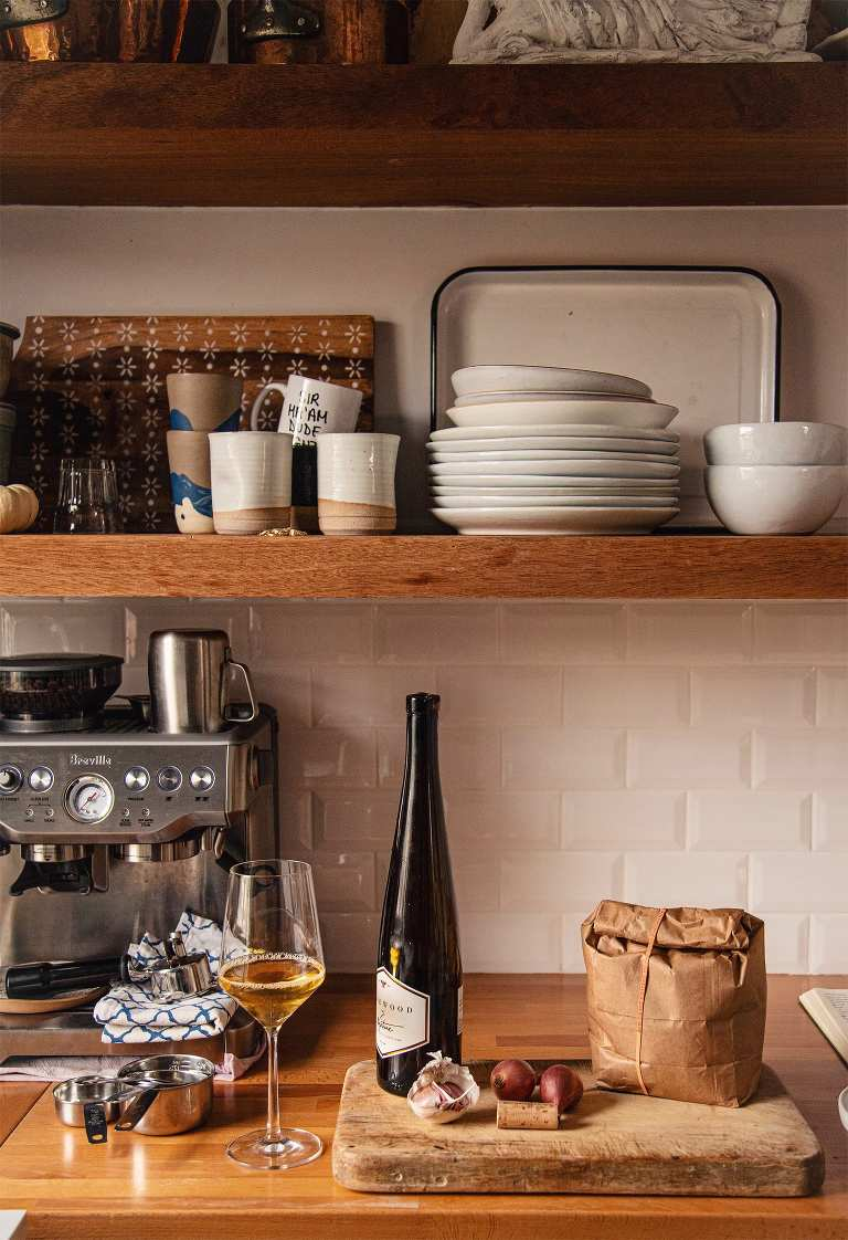 A shot of Laura's open kitchen shelving with a bottle of wine, a glass of wine, and a paper bag on the counter.