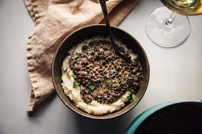 An overhead shot of a single serving of white wine lentils ladled on top of some creamy mashed cauliflower.