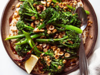 An overhead shot of a broccolini dish on a brown plate.