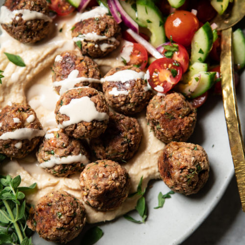 An overhead shot of vegan lemony oregano meatballs on a platter with hummus, tahini sauce, and a cucumber tomato salad.